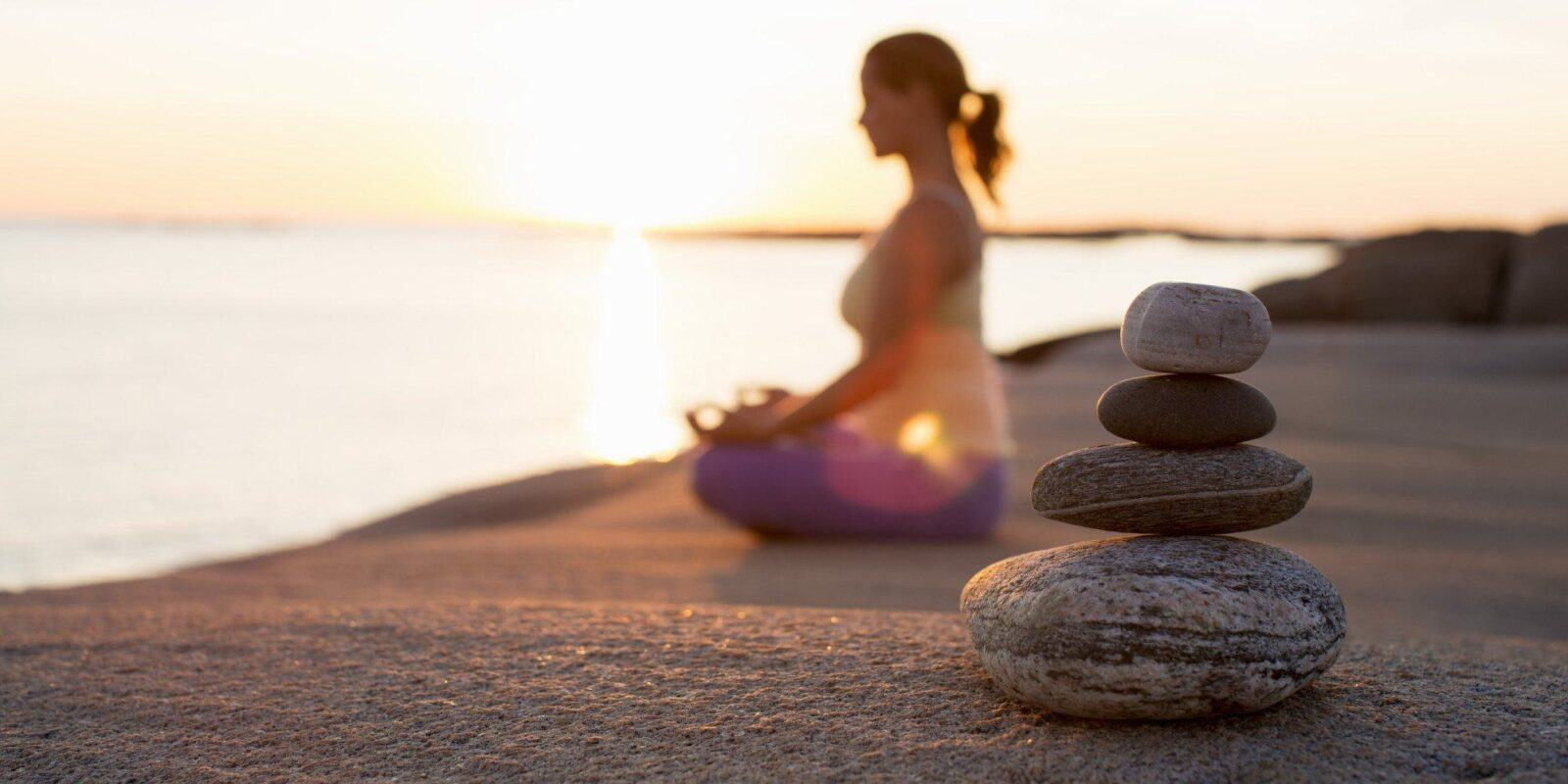 Side view of woman sitting in lotus position on lakeshore with focus on stack of stones